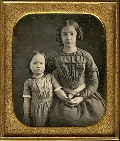 1850s. Older sister holding hand of younger sibling.