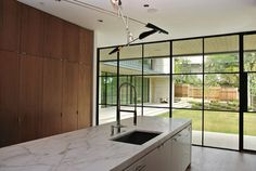 Contemporary kitchen with wood cabinets, marble kitchen counter top and lovely metal framed windows Marble Kitchen Counters, Wood Kitchen Cabinets, Home Design, Modern Design, Crittal Doors, Crittall Windows, Ideas Hogar, Large Windows, Steel Windows