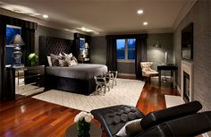 Black and gray color scheme give the room a modern feel while wood floors and lighting add warm touches.