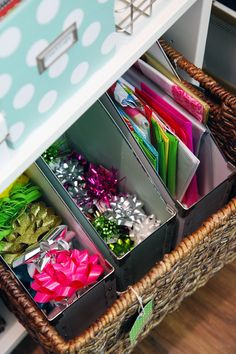 bows and gift bags inside magazine holders, inside a basket. containers within larger containers is good for organizing smaller items.
