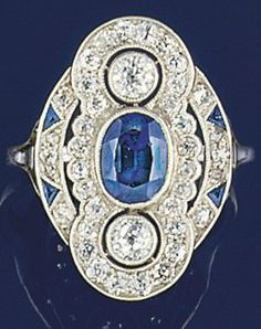 A Belle Epoque, sapphire and diamond ring. The central millegrain-set oval sapphire with old brilliant-cut diamond border and diamond circular cluster above and below to diamond and calibré triangular sapphire two row curved shoulders, circa 1910.
