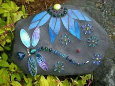Mosaic of dragon fly and flower on a stone