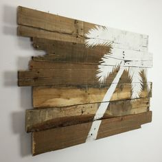 White Palm Tree on Natural Reclaimed Wood.   The size is roughly 32 x 21 x 2 Please massage me if you would like this piece in another color or size.  This wall art is made from reclaimed pallet wood. The years of weather and miles of wear creates a rustic look that simply can not be artificially created. Splits, cracks and nail holes build character.  This item has already been sold. Your purchase will be a very similar product. Reclaimed wood provides a unique appearance. Each item is a…