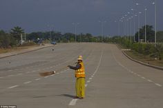 A street sweeper cleans this empty super-sized highway in the seemingly secluded capital c...