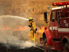 A CalFire firefighter uses a hose to put out a spot fire while battling the Rocky Fire in Lower Lake, Calif. More than 600 firefighters are battling the Rocky Fire that has burned more than 8,000 acres since it started. The fire is currently 0% contained and has destroyed three homes.  Justin Sullivan, Getty Images