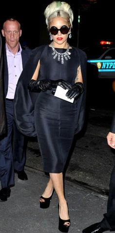 WHAT SHE WORE Lady Gaga made an N.Y.C. appearance in a Stephane Rolland cape dress, over-the-elbow leather gloves, Brian Atwood sandals and eye-popping jewelry. WHY WE LOVE IT La Gaga looked every inch a, well, lady in a luxe ensemble topped with a mint-blond bouffant.