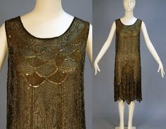 Beaded chiffon flapper dress. Sleeveless black silk with a pattern of scallops and geometric vertical bands in gold and crystal beads and iridescent sequins. It has a floral mid-band, scalloped hem with two slits to both front and back, and no under-dress.