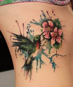 Watercolor hummingbird and flower side tattoo - Hummingbirds may be among the most studied families of birds. They are species of birds known for their ability to hover in mid-air by rapidly flapping their wings. The unique quality and ability of the birds makes them mysterious symbols in many folklore myths in culture and history of Native Americans, Aztecs. The symbolic qualities of the cute colorful bird make them favorite choice for tattoo design ideas.