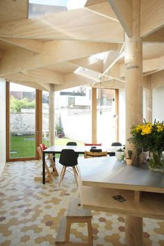 Columns and struts modelled on tree trunks and branches frame this extension to a home in Ghent