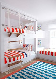 Red, white and blue boys' room features built-in shiplap bunk beds dressed in red, white and blue bedding accented with a white rope ladder as well as a third bed forming an L shape.