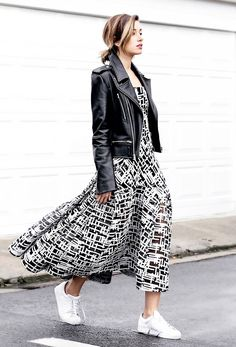 Blogger Chronicles of Her wears a printed maxi dress, white sneakers, and a clean black motorcycle jacket