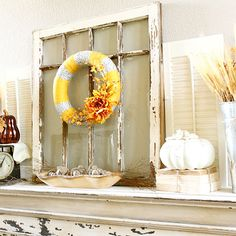 Yellow, Orange, and Gray Fall Mantel ~ Emily (decorchick.com) went with a rustic look for her fall mantel, using several natural elements. A wooden bowl holds acorns beneath an antique window frame. Faux pumpkins sit atop a stack of paperback books tied together with twine and also on a vintage scale with a piece of scrap burlap.