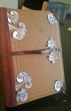 Kirjanmuokkausta altered art -teemalla. Kannessa peltitölkistä valmistettuja koristeornamenttejä ja nahkaa.