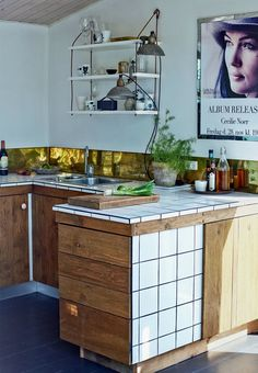 Kitchen made with recycled materials. Oak tree, white tiles, brass and old rustic lamps.