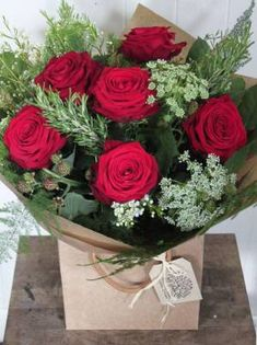 A deluxe red Rose bouquet arranged with Ammi, berries and mixed wild foliage.