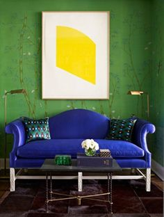 Saturated blue-purple loveseat against a forest green wall paper with a subtle forest motif.
