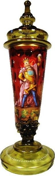 "Blown Amberina Glass 16 ½ "" Pokal. Rare technique that causes the glass color to gradually change from amber to ruby in color.  In the form of a drinking horn on a pedestal base.  The horn section is blown with interior circles that create great optics. Detailed enamel of King Gambrinus. Set on lid. The best of Moser glass."