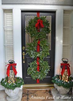 Triple wreath door hanger; lanterns full of twinkle lights on urns