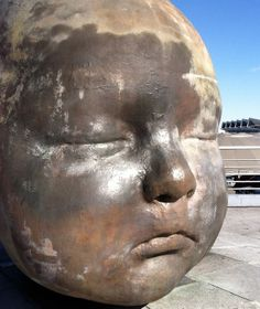"""Antonio Lopez Garcia's """" Day and Night """" X-Large baby head sculptures at the entrance to the Atocha train station. (Night sculpture in photo)"""