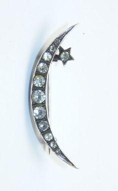 Star and moon brooch; silver set with crystal clear paste stones. 1900.