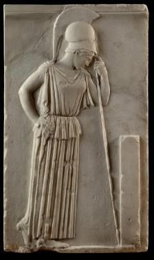 A carved relief in the Acropolis Museum  showing Athena; the Greek goddess of the arts of warfare wears her attribute of a helmet and leans on a spear.