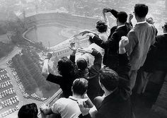 University of Pittsburgh students cheer as they look down on Forbes Field from the top of their campus's Cathedral of Learning as the Pirates are winning their first World Series in 35 years against the Yankees. In Game 7, Bill Mazeroski hit the first walk-off home run in World Series history, a shot over the left-field fence that gave the Pirates a 10-9 win.