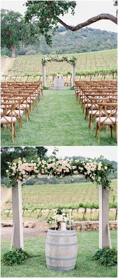California vineyard wedding ceremony, white and pastel pink florals, romantic wedding arbor, wine barrel, wooden cross-back ceremony chairs // Rachel Solomon