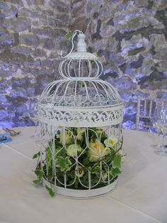 The bride chose birdcages, filled with an arrangement of roses and spring flowers, with trailing ivy round the outside.