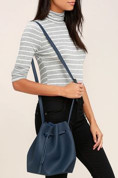 """Sling the Ride West Navy Blue Bucket Bag over your shoulder and head off to your next adventure! Pebbled vegan leather forms this versatile bucket bag with a crossbody design and a drawstring top. Faux suede interior. Shoulder strap measures 50""""."""