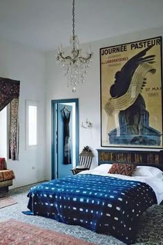 Fun, modern but cozy bedroom with indigo mud cloth throw, large-scale art, chandelier and lots of light and texture.