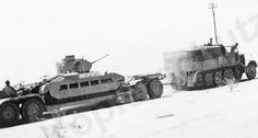 A Afrika Korps Famo SdKzf 9 with a Sd.Ah. 115 heavy trailer are recovering a British Matilda tank off the battlefield