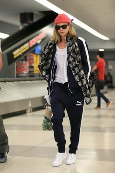 Pin for Later: Selena Gomez Isn't the First to Give Travel Sweatpants a High-Fashion Makeover Cara Delevingne Polish off a striped track set with a chiffon printed scarf and add a playful touch with a bright beanie.