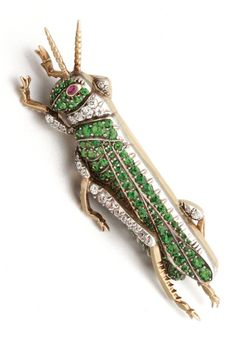 THE GRASSHOPPER Realistically modelled, the head and body set with 86 round green garnets, the neck and legs set with 25 old European-cut diamonds weighing approximately .50 carat, the eye set with a cabochon ruby, mounted in gold and silver as a brooch, brooch fitting detachable.