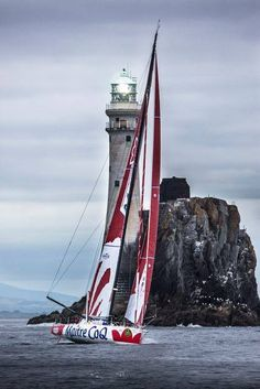 .lighthouse and graceful sails