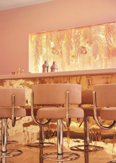 Pastel-toned pink walls are combined with Art Deco-style details in this champagne bar, to reflect the sparkling wines it will serve.