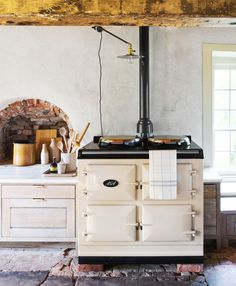 The cream-colored cast-iron cooker—William's favorite feature in the kitchen—sits on the footprint of the home's old fireplace hearth. Next to it, a restored beehive oven serves as a focal point in the cozy space.