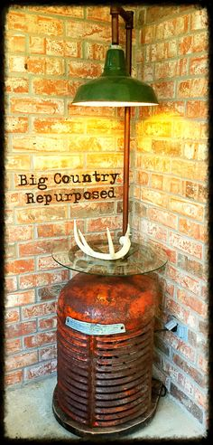 Rustic industrial table lamp.  The light is an antique porcelain barn light, and the base is an antique Case tractor grill. Also have an antique tractor steering wheel that is solid cast iron that makes a great shelf for a piece of glass. Would make a nice corner table or side table also.  $350