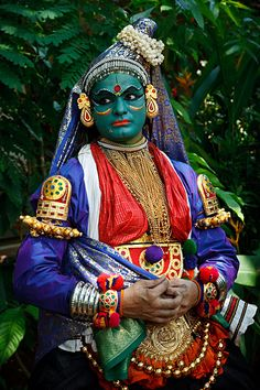Portrait of Kathakali dancer in full make-up and costume portraying a woman, demonstrating the double hand movement known as Samyutha Mudras