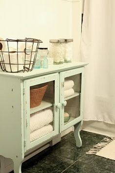 perfect inspiration for cabinent re-do in master bath. Love the glass doors and distressed look.