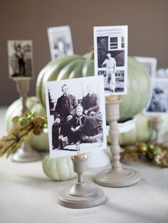 put a cork in candlestick holders, insert a paperclip into the cork and voila: instant photo / table number / place card holder