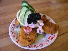 Danish open sandwich (smørrebrød) on dark rye bread with breaded fish, salad, cucumber, shrimps, black-colored lumpfish roe and tomato.