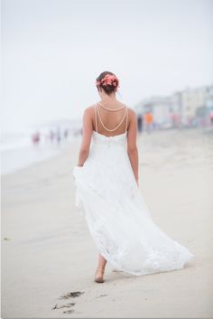 Carlsbad CA beach wedding with barefoot bride walking.  Love the coral flowers in her soft updo