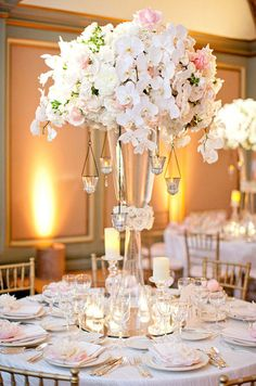 Orchids and hanging candles add elegance to this stunning centerpiece. Wedding Centerpieces, Flowers, Floral Arrangements