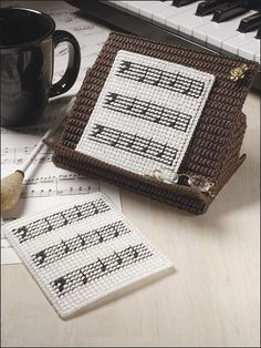 "Music lovers will love to make these coasters to set beside their piano. This e-pattern was originally published in Fun Time Coasters.Size: Coasters: 4"" x 4 1/2"". Holder: 4"" x 6 1/2"" x 6"". Made with 7-count canvas, 6-strand floss and plastic canvas yarn.Skill Level: Easy"