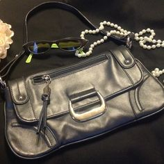 "REDUCED-DAISY FUENTES GUNMETAL GREY SHOULDER BAG! This bag is perfect when you are on the go.  It is stylish yet compact enough for dinner or a night out.  It has a slight metallic look to it that catches the light just right!  The silver fastener, zipper, and buttons add that finishing touch.  11 1/2"" at widest point, 6 1/2"" long, strap extends 8 1/2"".  Clean inside and out.  Falls right under the underarm area. Daisy Fuentes Bags Shoulder Bags"