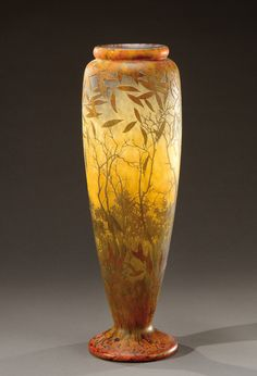 A slender lined glass vase acid-etched with trees and leaves on an opaque marbled background. Signed «Daum Nancy». Circa 1913.