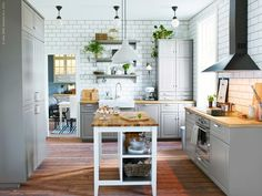pale grey kitchen with large subway tile walls and wood floors