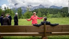 Germany's Chancellor Angela Merkel (C) gestures while chatting with US President Barack Obama sitting on a bench outside the Elmau Castle after a so-called outreach meeting at a G7 summit near Garmisch-Partenkirchen, southern Germany, on June 8, 2015.