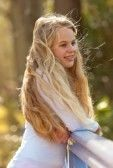 Happy young girl with long blonde hair on bridge in park. photo
