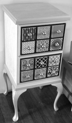 This was an old pine 2 drawer timber filing cabinet. I covered the flat surfaces with paintable, textured wallpaper. I then painted it, gave it some Queen Anne legs and then put tiles on to make it look like faux tiny drawers. I then added timber edging and brass knobs.